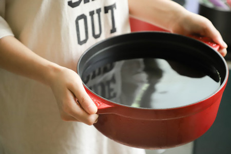 Hands holding a large pot of water