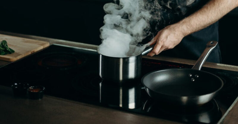 A pot and a pan on a glass top stove