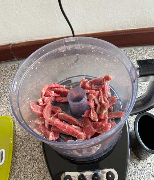 Perfectly sliced meat in the working bowl of a food processor