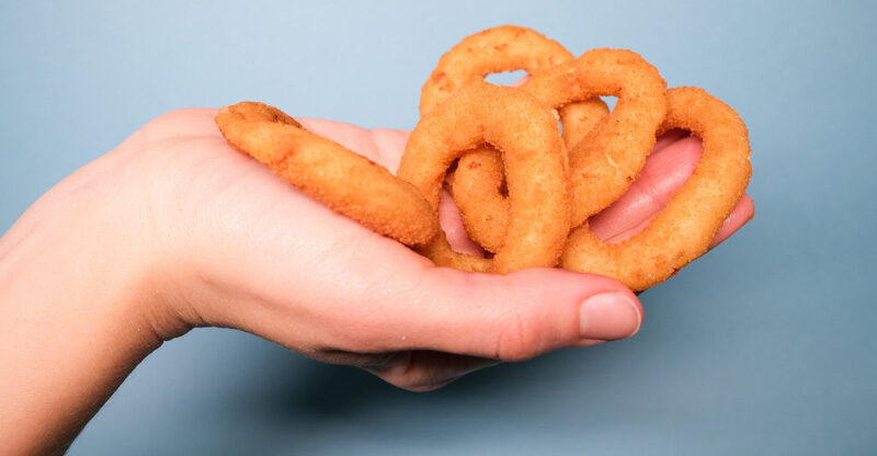 Hand holding golden, deep fried onion rings